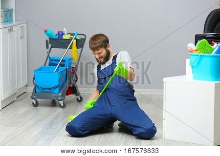 Funny young man with mop in office