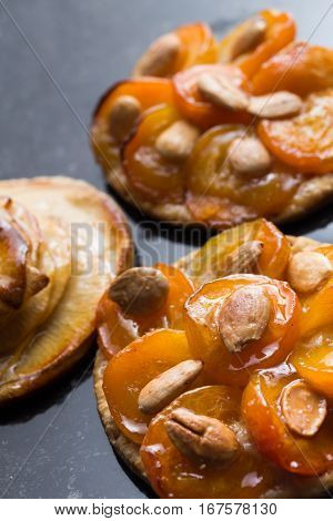 Tart with apricot and apple. Traditional french pie with fruits on dark marble background. Decorated almonds and mint leafs. Delicious dessert with copy space closeup.