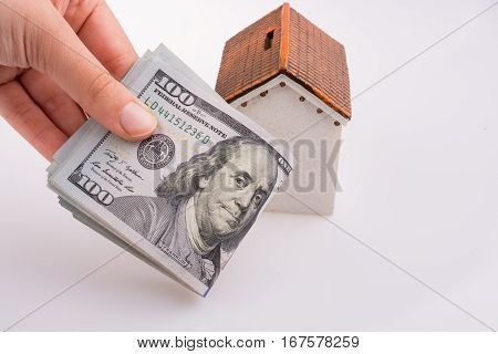 Human Hand Holding American Dollar Banknotes By The Side Of A Model House