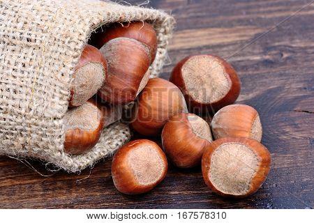 Hazelnuts in a jute sack on wooden table