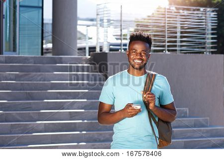 Smiling African Student Walking By Stairs With Bag And Smart Phone