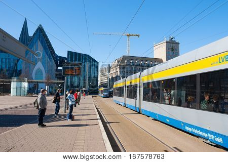 Leipzig, Germany - March 12, 2014: Modern street of Leipzig with tram people on the tram station.