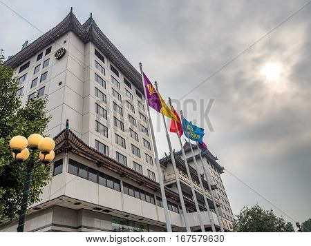 Beijing, China - Oct 30, 2016: Prime Hotel Beijing (Beijing Huaqiao Dasha) located on the 700-year-old Wangfujing Street. Image features a dramatic sky from a low-angle street view.