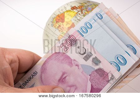 Hand Holding Turkish Lira Banknotes By The Side Of A Model Globe