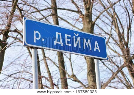A typical russian road sign with the designation of proximity to the river. The inscription in russian text translated as river Deima.