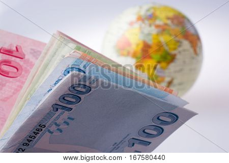 Turkish Lira Banknotes By The Side Of A Model Globe