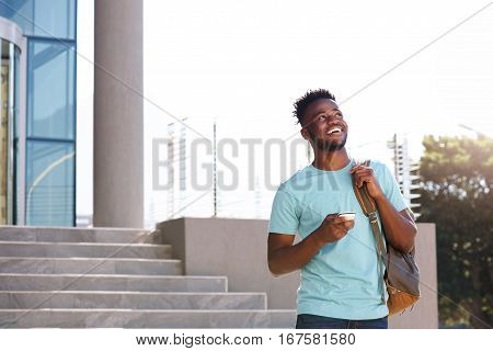 Male College Student Walking By Stairs With Bag And Smart Phone