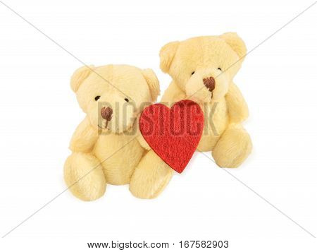 Two teddy bears sitting with red felt heart isolated over white. Valentine's Day and love concept.
