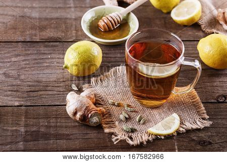 Hot tea with lemon ginger honey and cardamom over rustic wooden background close up