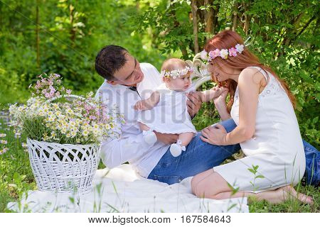 Family portrait outdoors picnic. Baby girl and her parents. Sunny Summer day Family Picnic. Happy family concept. Beautiful kid playing outside with parents.Young family spending time on a summer day