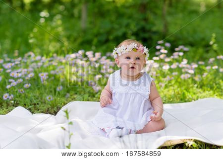 Baby girl outdoors portrait. Sunny Green Summer background. Portrait of beautiful angel girl playing outside