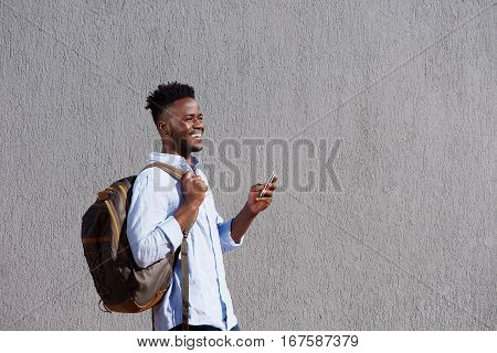 Handsome Black Man With Bag And Cellphone Walking By Wall