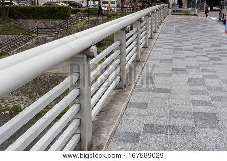 A modern urban walkway garded with railings on one side and beautiful decorated tree on the background can be seen in the picture.