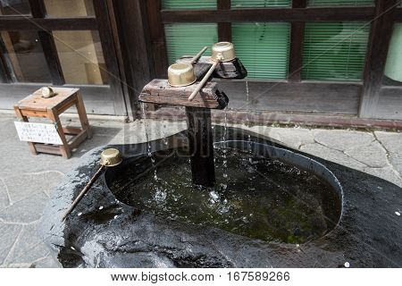 In the picture we can see water falling from a tap made up of wood and the water is collected in a place. A tool is also vissible in the picture.