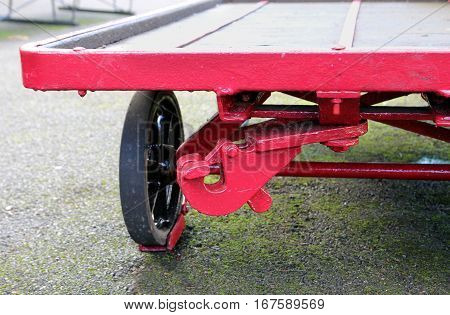 Axle and wheel of an old vintage retro red railway luggage trolley