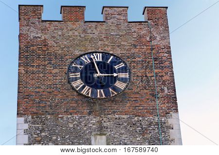 Clock tower of an old church with roman numerals on clock face