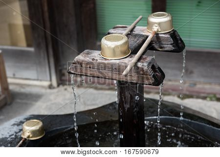 In the picture it is clearly seen that a water is falling from a wooden tap and the water is collected in a enclosed place.