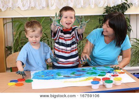 teacher two preschoolers and fingerpainting - education