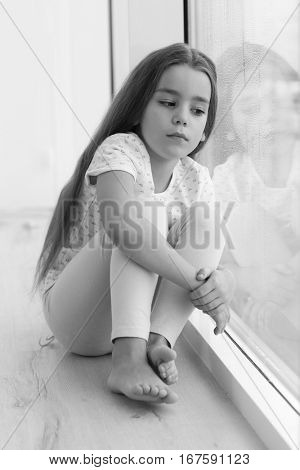 Little sad girl sitting on windowsill