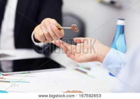Midsection of businessman giving out a key to woman