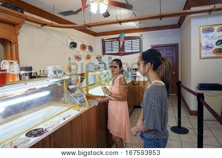 HARBOR SPRINGS, MICHIGAN / UNITED STATES - AUGUST 4, 2016: Customers prepare to buy ice cream at Kilwin's Ice Cream Shop in downtown Harbor Springs.