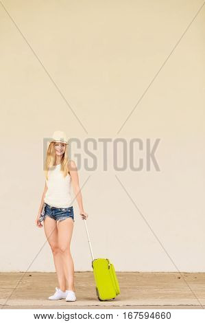 Travel adventure teenage journey concept. Woman wearing denim shorts white top and sun hat suitcase holding suitcase on wheels hitchhiking and relaxing during trip