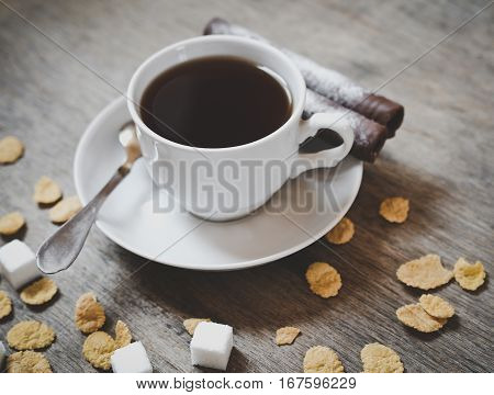 cup of coffee with sugar cubes and cor flakes on the wooden table