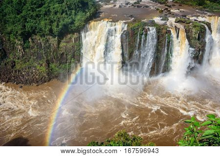 Rainbow and view of cascading water of Iguazu Falls with extensive tropical forest and raging river in Iguacu National Park, UNESCO World Heritage Site, Foz de Iguacu, Parana State, Brazil
