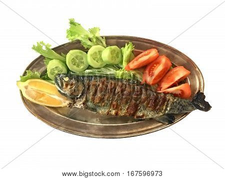 Fried (grilled) trout fish lay on a platter served with cucumber tomato lemon and herbs isolated on white background