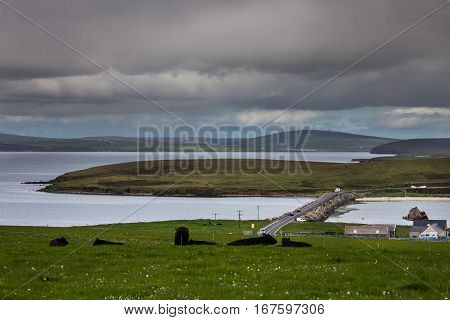 Orkneys Scotland - June 5 2012: Glims Hold Island in the center with dam leading to it. Green landscape with sea that looks like lakes. Heavy cloudy sky. White cars black cattle brown farm.