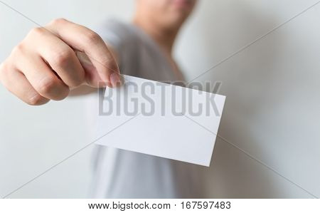 Close up hand of casual man holding white card on concrete wall background
