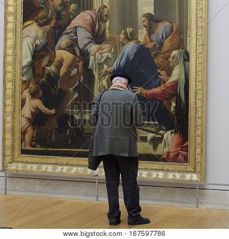 Paris, France, February 10, 2016: visitor looks at the pictures in Louvre, Paris, France