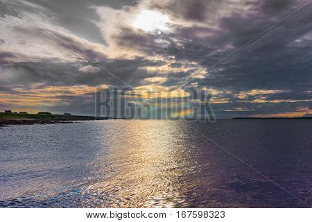 Orkneys Scotland - June 5 2012: Seascape looking at entrance to silver to mauve Atlantic Ocean under dark cloudy evening sky wherein waning sun creates colorful lights.
