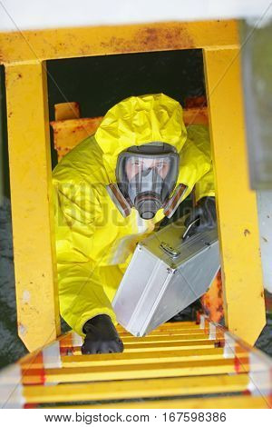 specialist in protective coverall and mask, with silver case,climbing on ladder above water