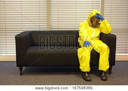 professional in protective clothing, mask and gloves, sitting and relaxing on the couch in office