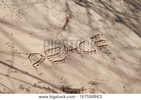 The word Peace written in sand on the beach