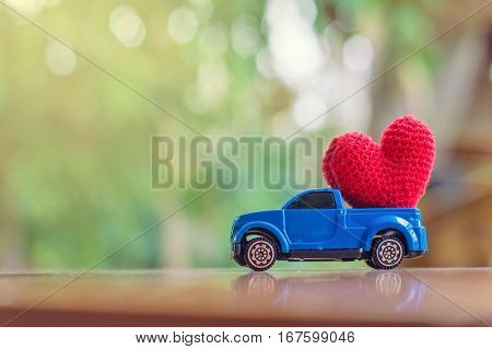 Blue toy car carring a red heart on the table for Valentine's day background