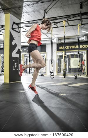Laughing girl jumps with a skipping rope in the gym on the background of the hanging TRX straps. She wears black shorts, red sleeveless and sneakers. Her hair is flying in the air. Vertical.