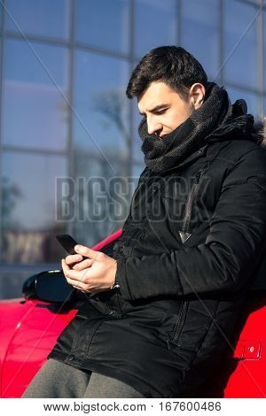 young man sending message near modern red sport car