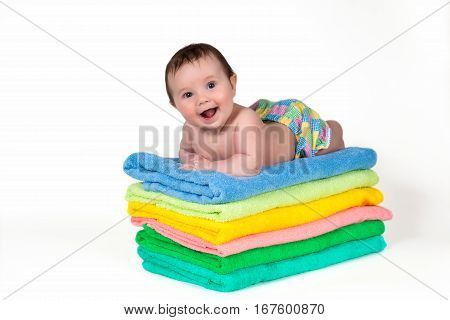 Newborn baby lying on a stack of towels.