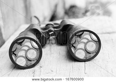 black binoculars. Big telescope on wooden background, money, coins