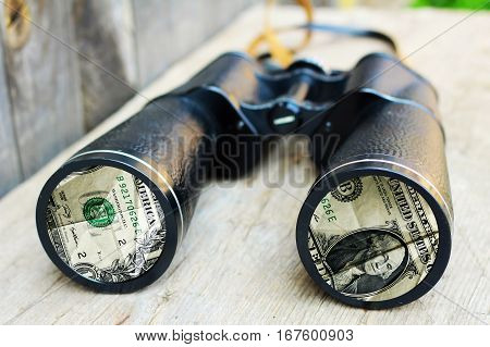 Binoculars and money, wealth attraction, one dollar