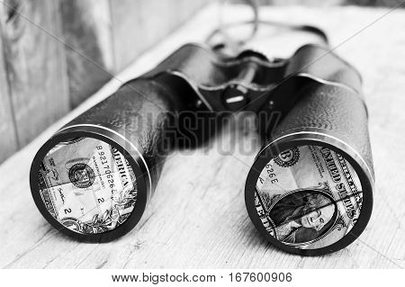 Binoculars and money, wealth attraction, black and white