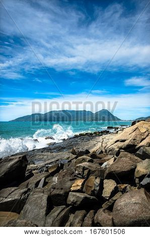 Coast full of rocks waves of sea water hitting the rocks blue sea and an island in the background. Beautiful summer day and very sunny. Morro das Pedras Florianopolis Brazil.