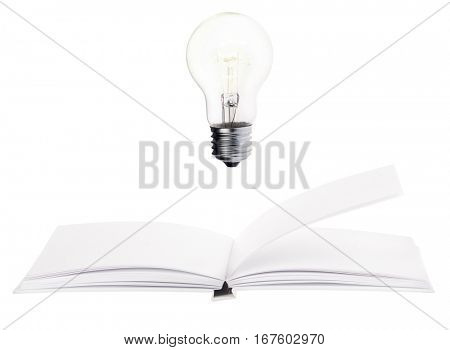 incandescent electric lamp and open blank book isolated on white background
