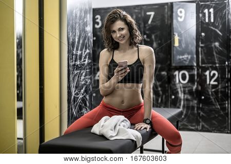 Happy curly woman in red pants and black top sits on the bench in the locker-room in the gym. She holds a mobile phone and looks into the camera with a smile. Horizontal.