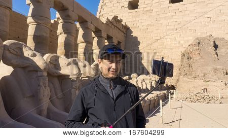 Happy man on holidays visiting ancient Egyptian temple in Luxor Egypt taking selfie shot using his mobile phone and selfie stick
