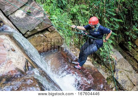 Beaufort,Sabah,Malaysia-Jan 28,2017: A adventurer canyoneer get ready to abseil down a waterfall in Beaufort,Sabah,Borneo.Waterfall Abseiling activity adventure getting famous in Sabah,Malaysia.