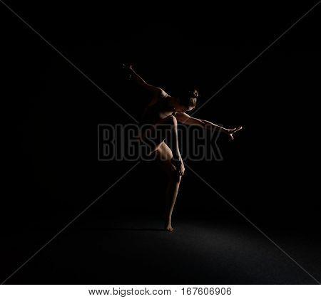 Graceful girl in beige body dancing emotionally alone in dark studio