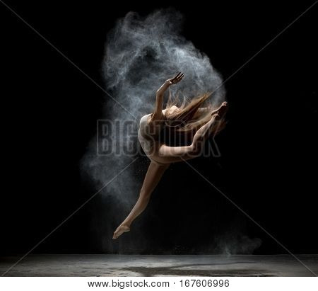 Slender girl dancing in cloud of white dust jumping gracefully studio shot